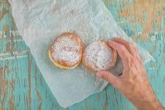 手为在土气桌上的甜含糖的多福饼到达 免版税库存图片