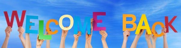 手举行五颜六色的词欢迎蓝天 免版税图库摄影