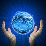 手举行发光的地球 高技术背景 免版税库存照片