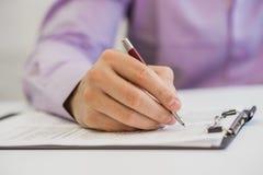手举行在笔记本和数据的一支黑笔报告了纸 免版税库存照片