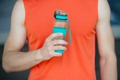 手举行嬉戏瓶水或体育饮料,男性身体背景 瓶水在肌肉男性手上 体育运动 库存图片