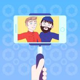 手举行巧妙的电话用两个行家人Selfie照片的棍子  免版税库存照片
