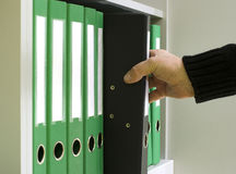 手人拔出从架子的一个文件夹 免版税库存照片