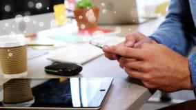 手人特写镜头写在他的手机的倾斜在书桌 影视素材