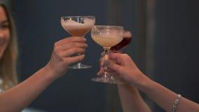 手使与鸡尾酒的玻璃叮当响的三名妇女关闭  女孩一起有庆祝 夫人一起获得一个乐趣 影视素材