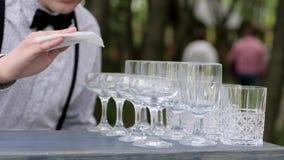 手侍酒者设置在酒吧,在酒吧柜台的行纯净的空的酒杯,在柜台的空白的觚的玻璃 股票录像