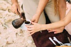 手供以人员倒从金属咖啡罐的土耳其咖啡入白色茶杯,妇女` s手帮助 免版税库存图片