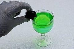 手倾吐一个小黑瓶毒物入与一份绿色饮料的一块玻璃 免版税图库摄影