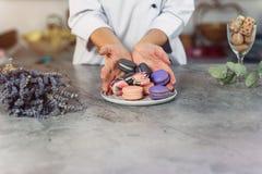 手倾吐色的macarons入在一张大理石桌上的一块白色板材 库存图片