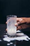 黑手党举行玻璃,溢出在桌上的白色牛奶 免版税库存图片