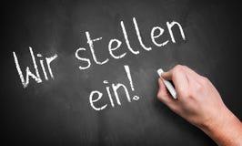 手写'我们聘用!'用德语 免版税图库摄影