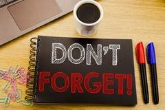 手写公告文本陈列不忘记 在木的笔记本书写的提示消息的企业概念 库存照片