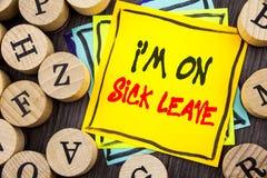 手写公告文本陈列我m是在病假 缺席企业照片陈列的假期的假日在办公室Sickne外面 库存照片
