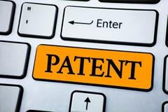 手写文本专利 概念赋予权力为使用卖做在橙色关键按钮写的产品的意思执照 免版税库存图片