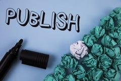 手写文本出版 概念意思使有用的资料对人发布在简单的蓝色backg写的一个书面产品 免版税库存图片