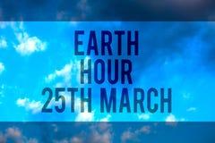 手写文本地球小时3月25日 概念意思对行星的标志承诺组织了全世界资金多行的文本deskt 免版税库存图片