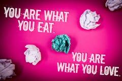 手写文本您是什么您吃 您是什么您爱 概念吃健康食物浅粉红色的地板的意思开始盘旋 免版税库存照片