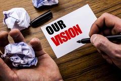 手写文本我们的视觉 在笔记本在木背景的便条纸写的销售方针视觉的概念与 免版税库存照片