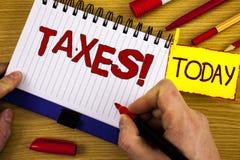 手写文本收税诱导电话 概念意思金钱由标志在手中写的它的支持的一个政府要求了 免版税库存图片