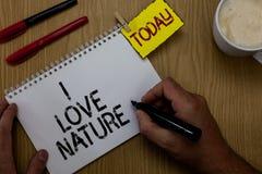 手写文本文字我爱自然 概念意思享受自然环境保存保护举行m的生态系人 库存照片