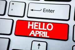 手写显示你好4月的公告文本 在keybord backgroun的红色钥匙写的春天欢迎的企业概念 库存照片