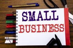 手写显示小企业的公告文本 Family的Owned在笔记本写的Company企业概念,木backgr 免版税库存照片