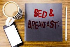 手写显示床早餐假日旅途旅行的写在笔记薄便条纸, w的公告文本企业概念 库存照片