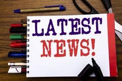 手写显示最新的新闻的公告文本 在笔记本写的新当前新的故事的企业概念,木backgr 库存图片