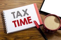 手写显示税时间的公告文本 征税在笔记薄在wo的便条纸写的财务提示的企业概念 免版税库存照片