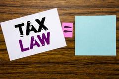 手写显示税法的公告文本 征税在木bac的稠粘的便条纸写的税收规则的企业概念 免版税库存照片