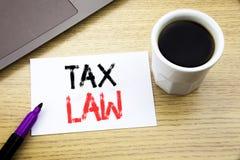 手写显示税法的公告文本 征税在木bac的笔记本书写的税收规则的企业概念 库存照片