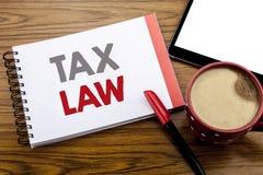 手写显示税法的公告文本 征税在笔记薄在木ba的便条纸写的税收规则的企业概念 库存照片