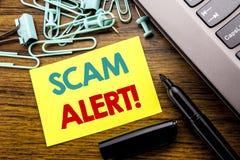 手写显示诈欺戒备的公告文本 在木ba的稠粘的便条纸写的欺骗警告的企业概念 库存照片