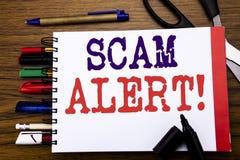 手写显示诈欺戒备的公告文本 在笔记本写的欺骗警告的企业概念,与o的木背景 免版税库存图片