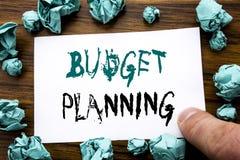 手写显示预算计划的公告文本 在稠粘的便条纸写的财政预算的企业概念,木头 库存照片
