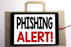 手写显示Phishing戒备的公告文本 在购物袋和片剂写的欺骗警告危险的企业概念 免版税库存图片
