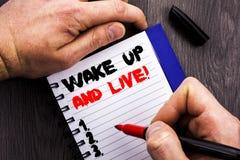 手写的文本标志陈列醒并且居住 概念性在Noteboo写的照片诱导成功梦想活生活挑战 库存图片
