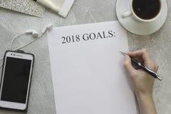 手写2018个目标、一个手机有耳机的和一个杯子cofee 图库摄影