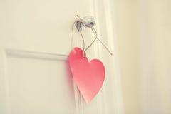 手制作了垂悬从门把手的心脏 免版税库存照片