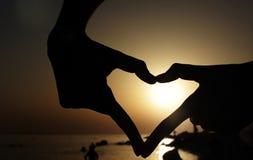 手剪影在爱的在日落天空 免版税图库摄影