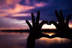 手剪影有心脏形状的与美好的颜色日落 免版税库存图片