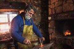 手动地伪造在铁砧的铁匠熔融金属在铁匠铺 库存照片