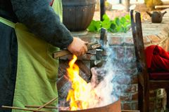 手动地伪造在铁砧的铁匠特写镜头熔融金属在铁匠铺车间 库存图片