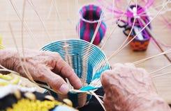 手动地编织竹篮子的女性手 免版税库存图片