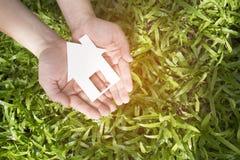 手反对绿色领域的举行房子 免版税库存照片