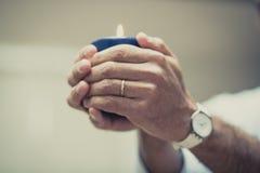 手和一个蓝色蜡烛 库存图片