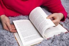 手和书特写镜头 一个女孩在床在家读一本书 概念剪切在老纸读取眼镜表面上写字染黄 花费与书的时间 免版税库存照片