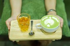 手和咖啡和热的绿茶青年人爱喝热 免版税库存照片