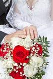 手和圆环在婚礼花束 免版税库存图片
