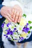 手和圆环在婚礼花束 免版税库存照片